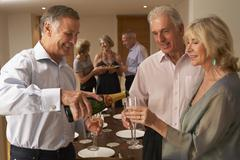 Man Serving Champagne To His Guests At A Dinner Party - stock photo