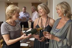 Woman Serving Champagne To Her Guests At A Dinner Party Stock Photos