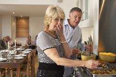 Couple Having Difficulty Cooking For A Dinner Party Stock Photos