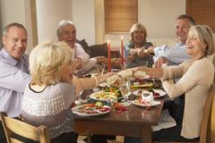 Friends Pulling Christmas Crackers At A Dinner Party - stock photo