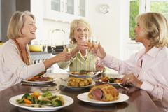 Friends Enjoying Lunch At Home Together Stock Photos