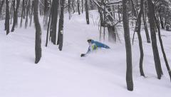 SLOW MOTION: snowboarder doing powder turn in forest Stock Footage
