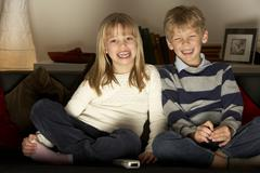 Brother And Sister Watching Television Stock Photos