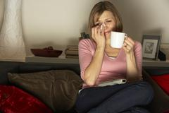 Woman Relaxing With Cup Of Coffee Watching Television Stock Photos