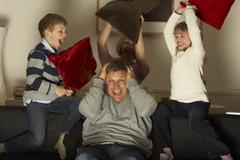 Parents And Two Children In Pillow Fight Stock Photos