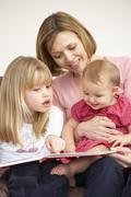 Mother And Daughters Reading Book Stock Photos