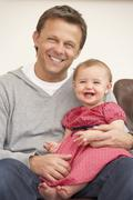 Father And Baby Daughter On Sofa - stock photo