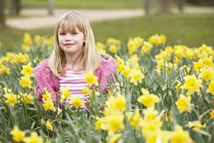 Young Girl Surrounded By Daffodils - stock photo
