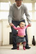 Father Helps Baby Daughter With Walking Stock Photos