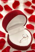 Diamond Ring In Heart Shaped Box Surrounded By Rose Petals Stock Photos