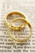 Two Wedding Rings Resting On A  Bible Page - stock photo