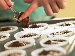 Putting Chocolate Cupcake Mix Into Baking Tin Stock Photos