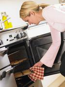 Woman Taking Cookies Out Of Oven Stock Photos