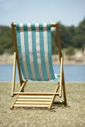 Lone Beach Chair Sitting Next To Water Stock Photos