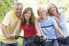 Family Cycling Through A Park Stock Photos
