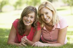 Woman Lying On The Ground With Her Teenage Daughter - stock photo