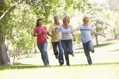 Family Running Through A Park - stock photo