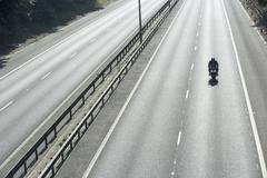 Lone Biker On An Empty Highway Stock Photos