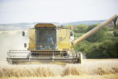 Combine Harvester Working In Field - stock photo