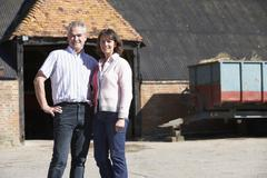 Farmer And Wife Standing In Front Of Farm Buildings - stock photo