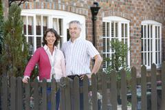 Farmer And Wife Standing In Front Of Farmhouse Stock Photos
