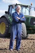 Stock Photo of Driver Standing In Front Of Tractor