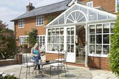 Exterior Of House With Conservatory And Patio - stock photo