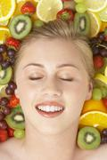 Portrait Of Young Woman Surrounded By Fruit Stock Photos
