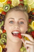 Portrait Of Young Woman Eating Strawberry - stock photo