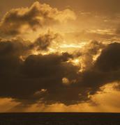 Moody dark clouds at sunset Stock Photos