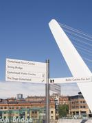 gateshead millennium bridge and signpost, newcastle on tyne - stock photo