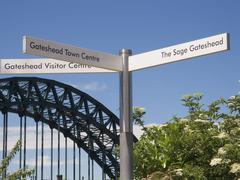 signpost with tyne bridge, newcastle on tyne, tyne and wear, england - stock photo
