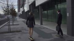 Businessman and businesswoman longboard skating in big city Stock Footage