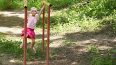 Girl hangs on bars, shakes in different directions and jumps off Stock Footage