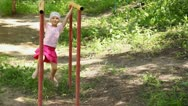 Stock Video Footage of girl hangs on bars, shakes in different directions and jumps off