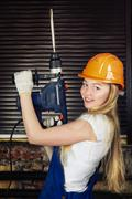 beautiful woman with heavy drill - stock photo