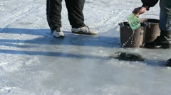 Man draw water ice hole pour bucket winter skate site people Stock Footage