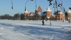 Man carry ski frozen lake Trakai castle winter active recreation Stock Footage