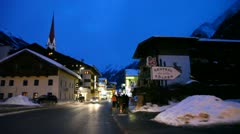 Cars go on road in Soelden along shops and hotels Stock Footage