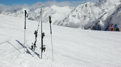 Skis and ski sticks stick out of snow on mountain slope Stock Footage