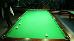 Player walk around green billiard table in dark club Stock Footage