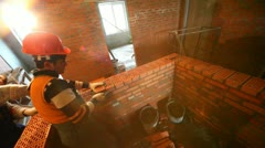 Two labourers build wall in room at construction site Stock Footage