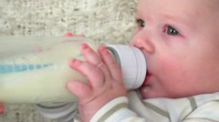 Little baby boy lies on cloth and drinks milk from bottle Stock Footage