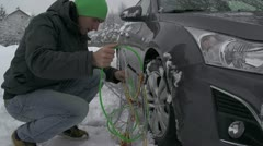 Man putting snow chains on a car Stock Footage