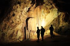 Silhouette of 3 figures in a Cavern Stock Photos