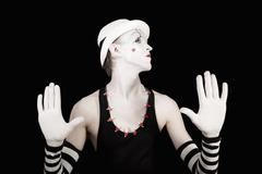 Ape mime in striped gloves and white hat on black background Stock Photos
