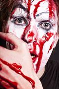 mime with blood on face and hand - stock photo