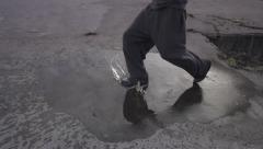 SLOW MOTION: running through a puddle Stock Footage