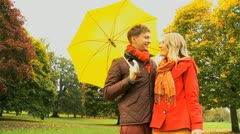 Couple Sheltering Fall Weather in Park Stock Footage