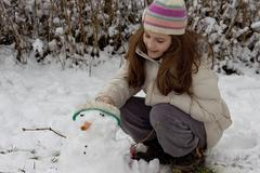 Girl makes a snowman Stock Photos